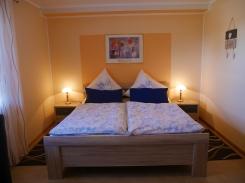 Schlafzimmer mit Doppelbett und Fenster zum Garten